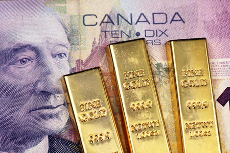A close up image of a purple Canadian ten dollar bill with three small gold ingots
