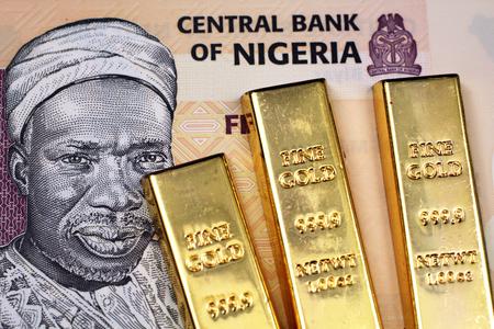 A five Nigerain naira bank note with three small gold bars close up in macro