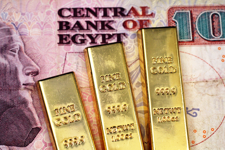 A close up image of three small gold bars on a ten Egyptian pound bank note in macro Stock Photo