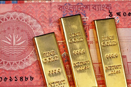 A close up image of a red ten taka note from Bangladesh with three small gold bars in macro