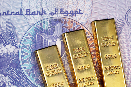A close up image of three small gold bars on a twenty five Egyptian piastres bank note in macro