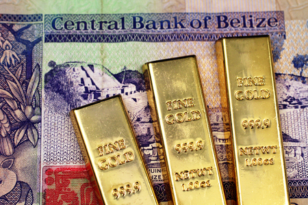 A close up image of three gold bars close up with a two dollar bill from Belize in macro Stock Photo