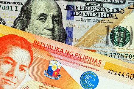 A close up image of an orange Filipino twenty peso note with an American blue one hundred dollar bill in macro Banco de Imagens