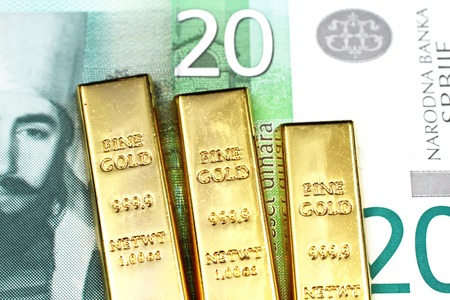 A close up image of a twenty Serbian dinar bank note with three small gold bars in macro