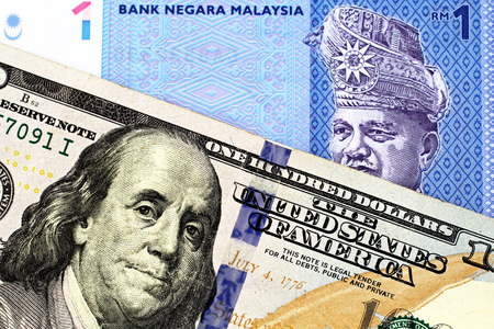 A blue one ringgit bank note from Malaysia with an American one hundred dollar bill in macro Imagens