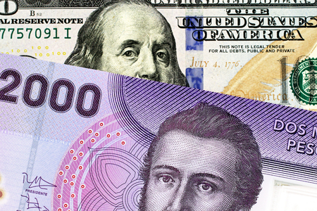 A close up image of a purple Chilean two thousand peso bank note with a blue, crisp American one hundred dollar in macro Banco de Imagens