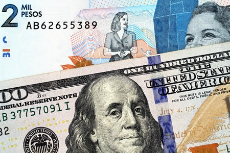 A macro image of a blue, two thousand Colombian peso bank note with a blue, crisp American one hundred dollar bill close up