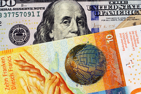 A yellow Swiss ten franc note with a blue one hundred American dollar bill close up in macro