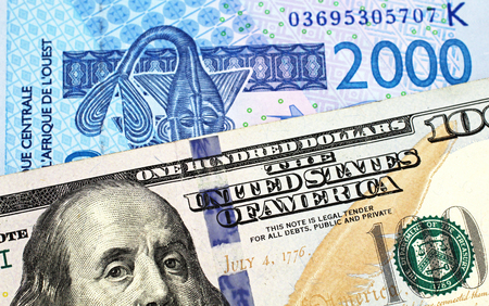 A close up image of a 2000 West African Franc banknote with a new, blue American one hundred dollar bill in macro