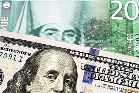 A close up image of an American one hundred dollar bill with a twenty dinar bank note from Serbia in macro Stock Photo