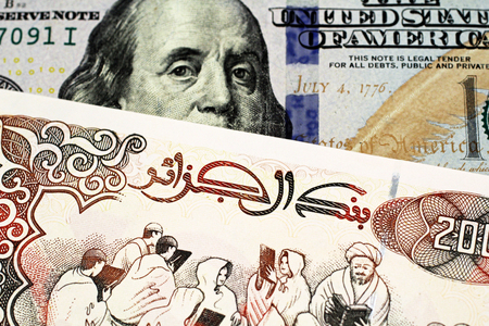 A close up image of an American one hundred dollar bill with an Algerian two hundred dinar bank note in macro Stockfoto
