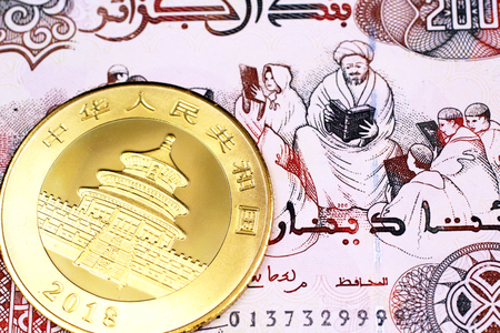 A macro image of a 200 Algerian dinar note with a gold, panda coin from China close up
