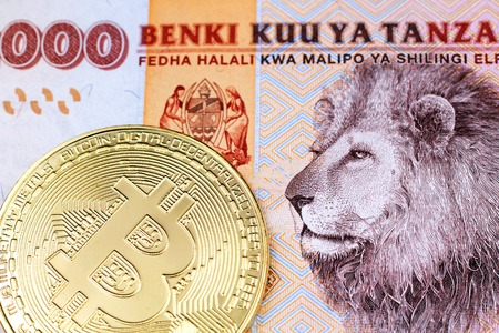 A close up image of an orange, Tanzanian two thousand shilling note with a shiny, gold physical bitcoin in macro