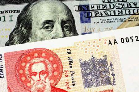 A red Bulgarian one lev bank note with an American one hundred dollar bill close up in macro