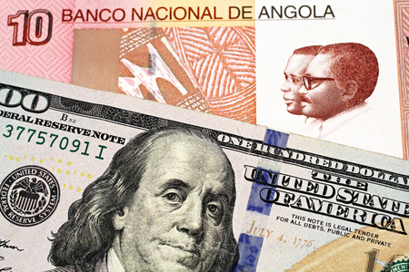 A macro image of a colorful Angolan ten kwanza bill with an American one hundred dollar bill close up Stock Photo