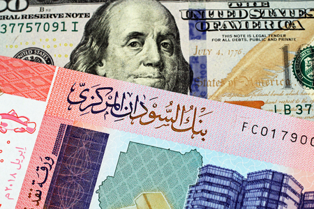 A close up image of an American one hundred dollar bill with a colorful fifty pound note from Sudan in macro