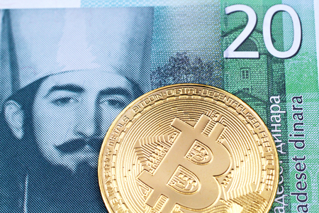 A close up image of a golden physical Bitcoin with a green twenty Serbian dinar bank note in macro Stock Photo