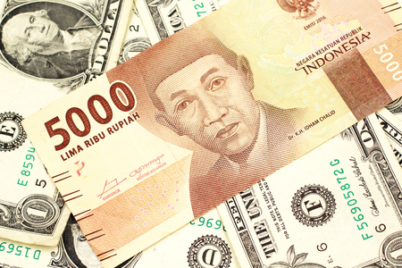 An orange, five thousand Indonesian rupiah bank note with American one dollar bills close up in macro
