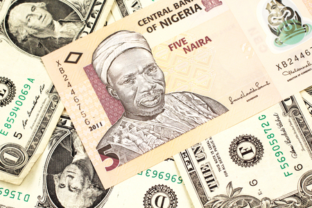A close up image of a peach colored, five Nigerian naira bank note on a background of American one dollar bills Stock Photo - 124625081