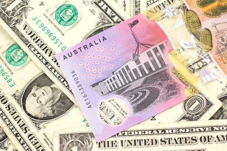 A close up image of an Australian five dollar bill with United States one dollar bills in macro