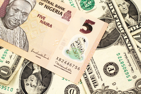 A close up image of a peach colored, five Nigerian naira bank note on a background of American one dollar bills Stock Photo