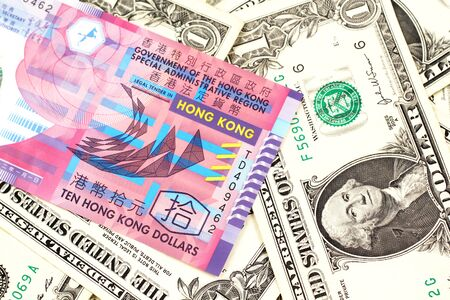 A close up image of a colorful Hong Kong ten dollar bill in macro on a bed of American one dollar bills 免版税图像