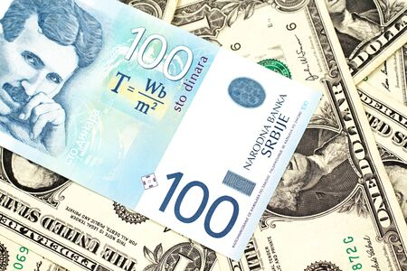 A close up of a blue and white, one hundred Serbian dinar bank note on a background of American one dollar bills 版權商用圖片