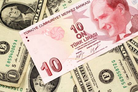 A close up image of a red ten Turkish lira bank note on a background of American one dollar bills in macro 免版税图像