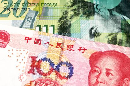 A twenty shekel note from Israel close up in macro with a red, Chinese one hundred yuan renminbi bank note