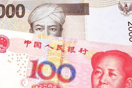 A gray two thousand Indonesian rupiah bank note with a red, one hundred Chinese yuan Stock Photo