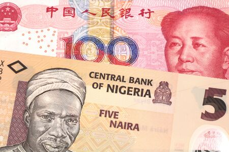 An orange five naira note from Nigeria with a red, one hundred yuan renminbi note from China close up in macro 스톡 콘텐츠