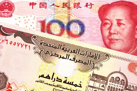 A red, Chinese one hundred yuan renminbi bank note with a five dirham bank note from the United Arab Emirates close up in macro