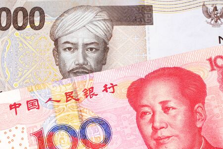 A gray two thousand Indonesian rupiah bank note with a red, one hundred Chinese yuan 版權商用圖片