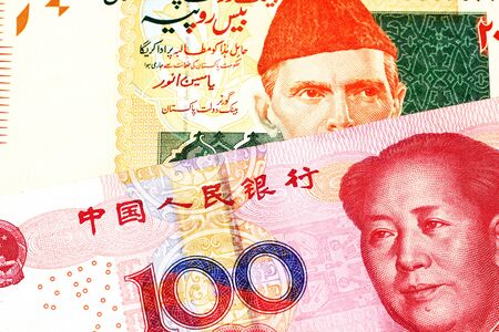 An orange and green twenty Pakistani rupee bank note with a red one hundred Chinese yuan bank note in macro
