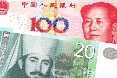 A twenty Serbian dinar bank note, close up in macro with a red Chinese one hundred yuan renminbi bank note