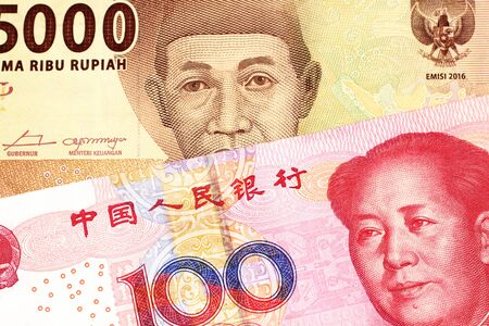 An orange five thousand Indonesian rupiah bank note with a red, one hundred Chinese yuan Stock Photo