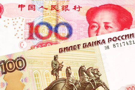A close up image of a one hundred Russian ruble bank note close up with a red one hundred Chinese yuan bank note