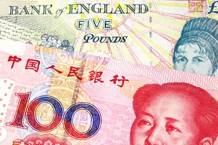 A five pound British pound sterling with a red, one hundred yuan Chinese renminbi bank note close up in macro