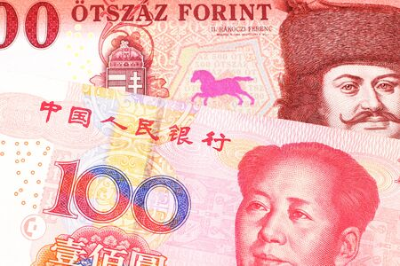 A close up image of a red, one hundred Hungarian forint bill close up with a red, one hundred yuan renminbi Chinese bank note in macro Foto de archivo