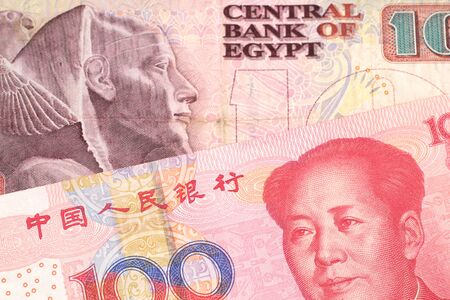 A ten Egyptian pound bill with a red, one hundred yuan Chinese renminbi note close up in macro