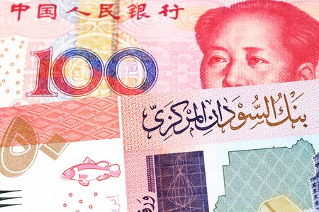 A one hundred yuan, Chinese renminbi bill with a fifty pound note from Sudan close up in macro Stock Photo