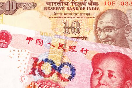 An orange, Indian ten rupee bill, close up with a red, one hundred yuan Chinese renminbi note 免版税图像