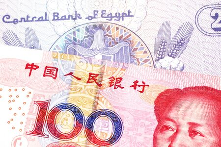 A close up image of a purple, twenty five Egyptian piastres note close up in macro with a red, Chinese one hundred yuan renminbi bank note