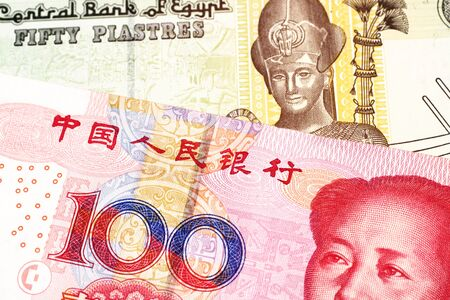A close up image of a colorful fifty Egyptian piastres note close up in macro with a red, Chinese one hundred yuan renminbi bank note Foto de archivo