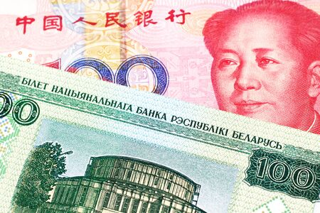 A close up image of a one hundred yuan note from the People's Republic of China with a one hundred ruble note from Belarus Foto de archivo