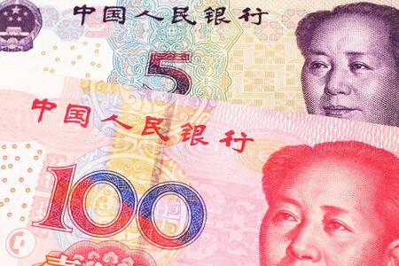 A close up image of a five yuan note from the People's Republic of China along with a red, one hundred yuan note from China