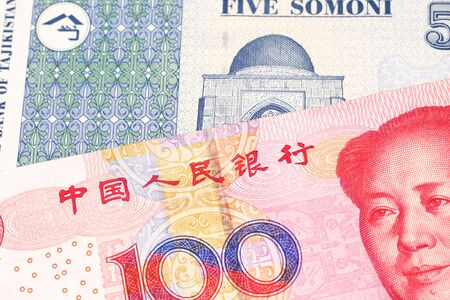 A close up image of a one hundred yuan note from the People's Republic of China along with a five somoni note from Tajikistan Stock Photo