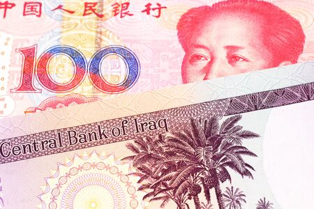 A purple fifty dinar note from Iraq close up with a red, one hundred yuan renminbi note from the People's Republic of China