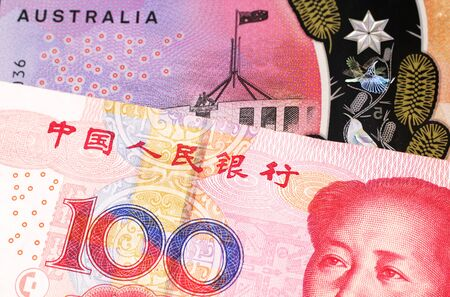 A close up image of a purple, five Australian dollar note close up, in macro with a red, one hundred yuan renminbi banknote from the People's Republic of China