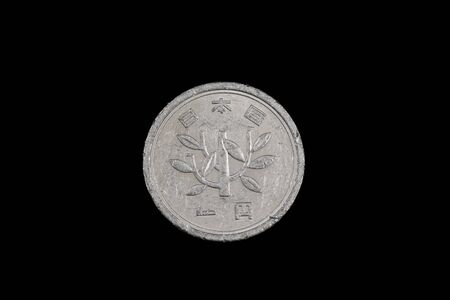 A close up, macro image of silver, Japanese one yen coin isolated on a black background